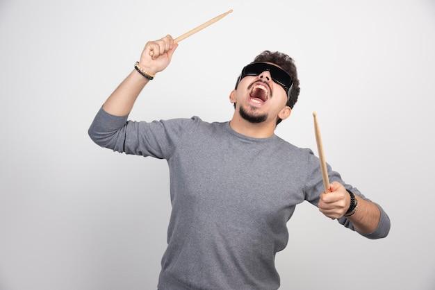 Een drummer met een zwarte zonnebril die drumstokken vasthoudt en er erg energiek uitziet.