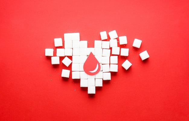 Een druppel bloed op een hart gemaakt van pure witte suikerklontjes