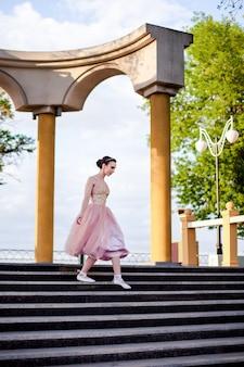 Een dunne vrouwelijke ballerina in een roze zijden jurk en spitzen met linten daalt sierlijk naar beneden...