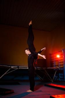 Een duo van acrobaten die een dubbeltruc uitvoeren. een vrouw in gymnastiekoverall en een man in sportkleding. zeer flexibele circusartiesten.