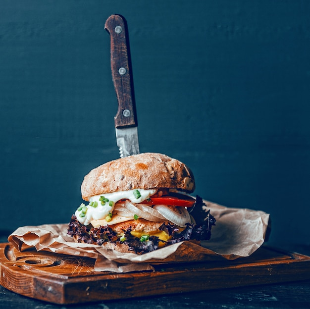 Een echte hamburger op een houten achtergrond. met een grote en sappige kotelet malse kaassaus en mosterd. rustiek