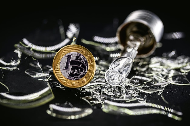 Een echte munt met een kapotte gloeilamp, concept van hoge elektriciteitskosten of risico op black-out in brazilië