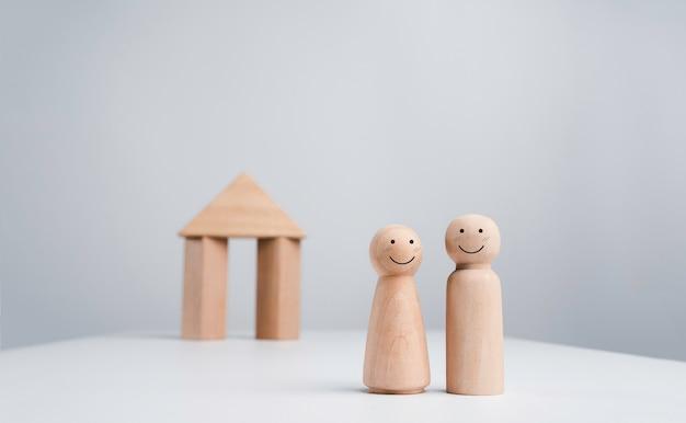 Een echtpaar begint een leven samen met het vastgoedbeleggingsconcept. het blije gezicht houten menselijke paar staande voor een houten huis miniatuur op witte achtergrond, minimalistische stijl.