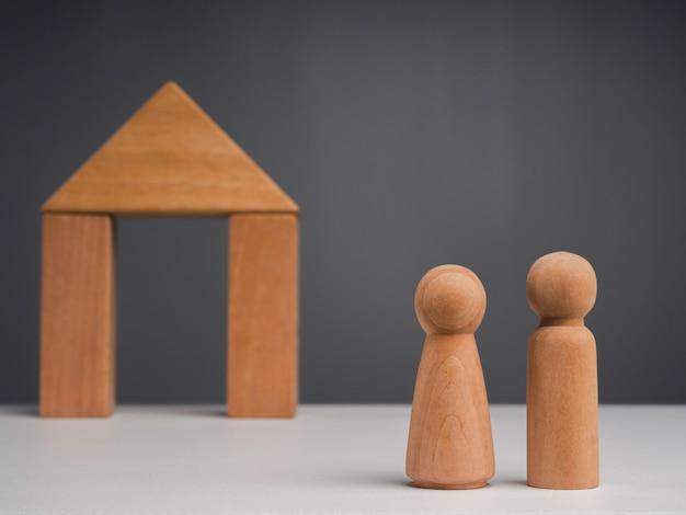 Een echtpaar begint een leven samen met het vastgoedbeleggingsconcept. het houten menselijke paar dat voor een houten huisminiatuur staat op een grijze achtergrond, minimalistische stijl.