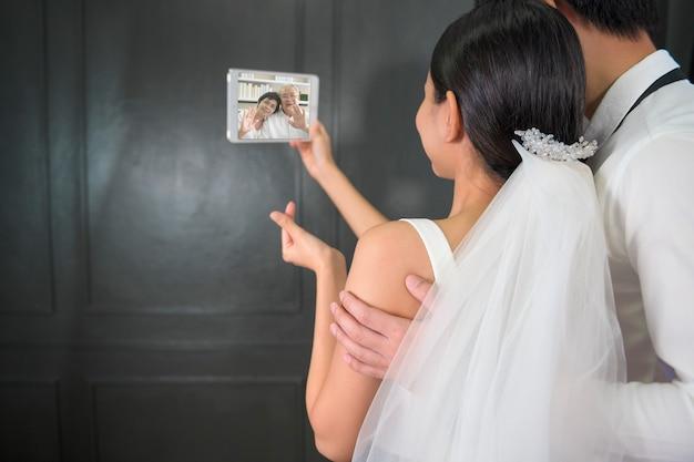 Een echtpaar in een bruidsjurk voert een videogesprek met de ouders in quarantaine