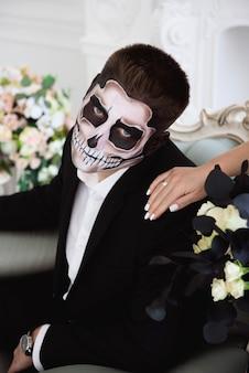 Een echtpaar met skelet maakt halloween of allerzielen goed