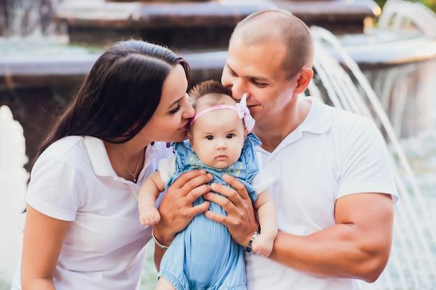 Een echtpaar zittend op de rand van een stad fontein, een kind in zijn armen, concept van liefde