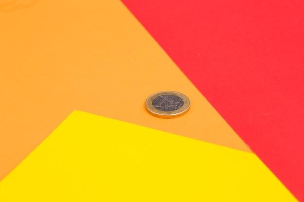 Een een-euromunt op rood; gele en oranje achtergrond