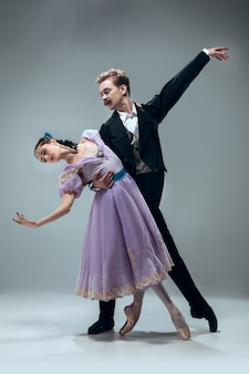 Een eenheid. mooie eigentijdse balzaaldansers die op grijze muur worden geïsoleerd. sensuele professionele artiesten die walz, tango, slowfox en quickstep dansen. flexibel en gewichtloos.
