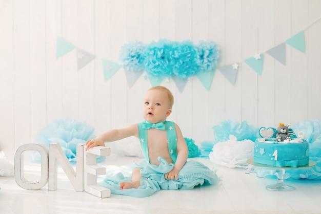 Een eenjarige jongen in een blauwe korte broek en een vlinderdas viert zijn verjaardag naast de letters one op een standaard en een decoratie voor zijn feest