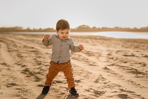 Een eenjarige jongen leert lopen in het zand bij de rivier.