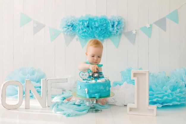 Een eenjarige jongen probeert zijn eerste verjaardagstaart