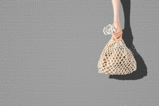 Een eenvoudig abstract beeld van de hand met een eco-tas van mesh-katoen tegen de kleurenmuur, recyclen zonder afval
