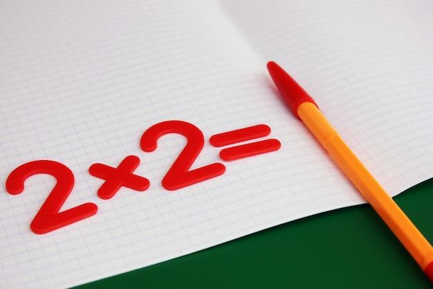 Een eenvoudig wiskundig voorbeeld in een schoon schoolnotitieboekje. terug naar school.