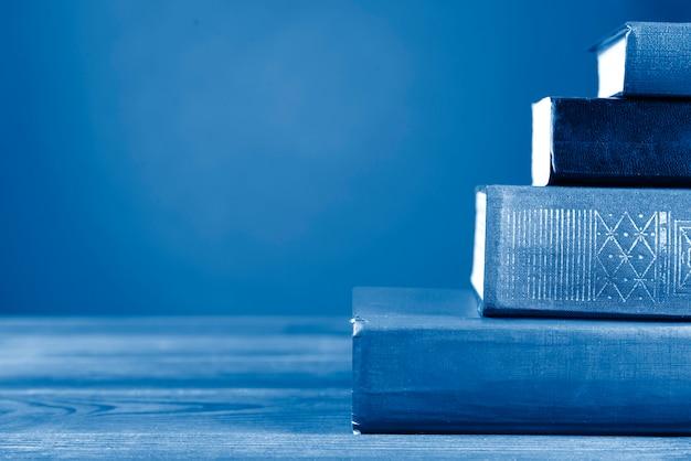 Een eenvoudige compositie uit vele hardback-boeken, getint in klassieke blauwe kleur. terug naar school. kopieer ruimte. onderwijs