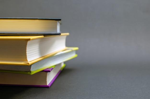 Een eenvoudige compositie van veel boeken met harde kaft op een zwarte achtergrond. terug naar school. onderwijsconcept. ruimte kopiëren.