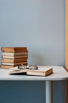 Een eenvoudige compositie van verschillende oude boeken op een witte moderne tafel met lichtgrijze achtergrond, terug naar school, onderwijs. een boek wordt geopend met een bril erop