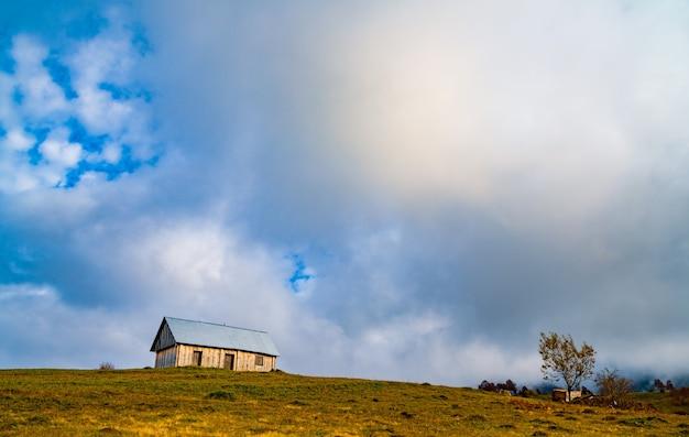 Een eenzaam grijs huisje staat op een frisse natte groene weide te midden van een dichte grijze mist