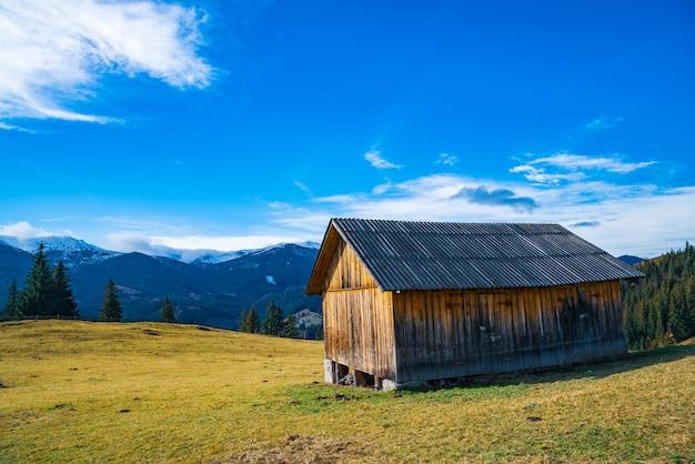 Een eenzaam klein grijs huis staat op een frisse, natte groene weide te midden van een dichte grijze mist