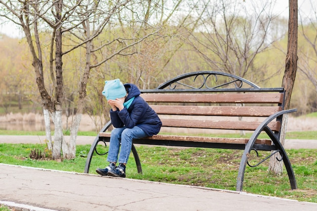 Een eenzaam meisje zit voor haar gezicht met haar handpalmen op een bankje in het park. mentale gezondheid