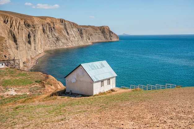 Een eenzaam rustig huis aan de rand van een klif met een schilderachtig berglandschap