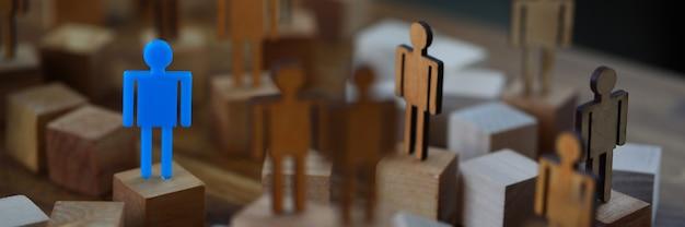 Een eenzame figuur van speelgoed blauwe man staat in de menigte