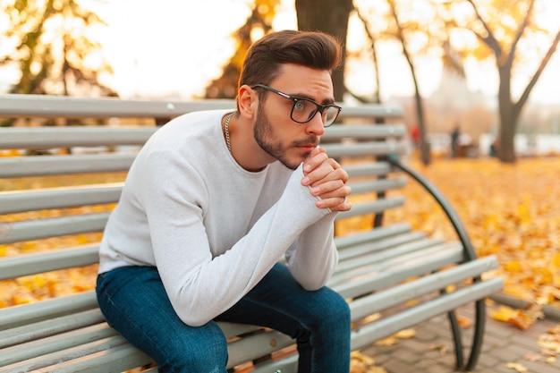 Een eenzame knappe man zit verdrietig in het park op een bankje.