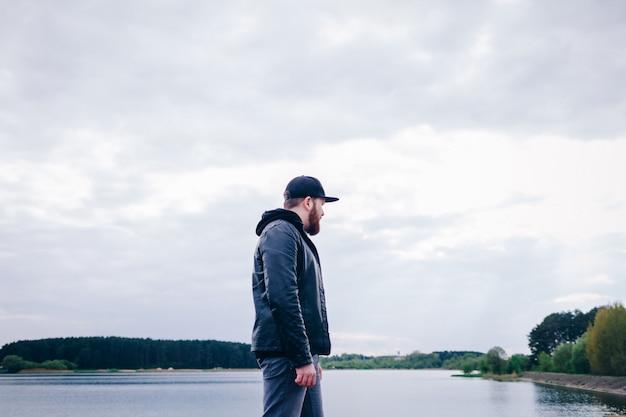 Een eenzame man in een leren jas in de buurt van de rivier