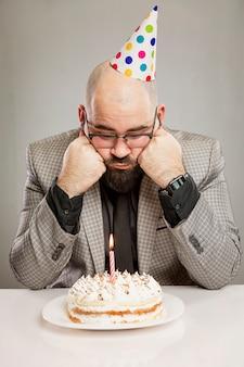 Een eenzame man in een pet zit voor een cake met een kaars. trieste verjaardag. grijze muur. verticaal.