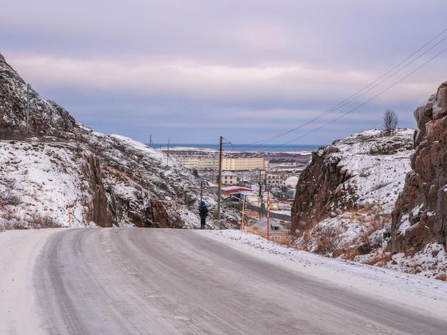 Een eenzame man loopt over een kronkelende weg tussen de arctische heuvels. teriberka.