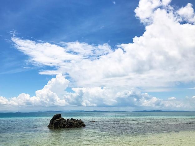 Een eenzame rots aan de zee met wolken op de blauwe hemelachtergrond op een zonnige dag