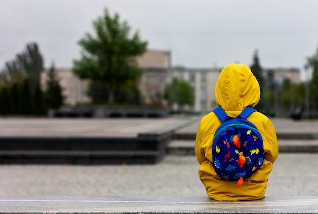 Een eenzame trieste jongen in een lege stad isolement pandemie quarantaine denken alleen jongen in een gele regenjas