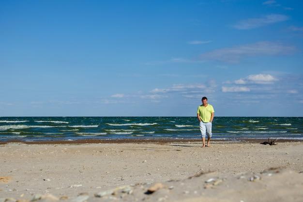 Een eenzame, trieste man loopt langs de kust en verlangt. men dwaalt over een verlaten zomerstrand en denkt aan het leven. het concept van slecht humeur, depressie, het verbreken van liefdesrelaties. kopieer ruimte
