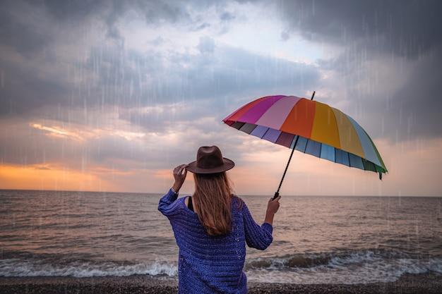 Een eenzame vrouw met een hoed en een regenboogparaplu staat alleen aan zee tijdens een regenachtige, bewolkte, humeurige dag.