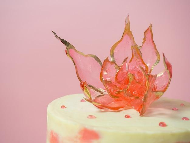 Een eetbare rode bloem bovenop een isomaltcake op een roze achtergrond