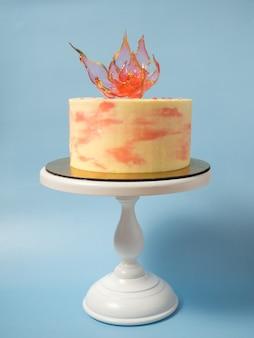 Een eetbare rode isomaltbloem bovenop een cake op een blauwe achtergrond
