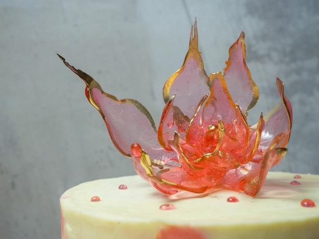 Een eetbare rode isomaltbloem bovenop een cake op een lichte betonnen ondergrond