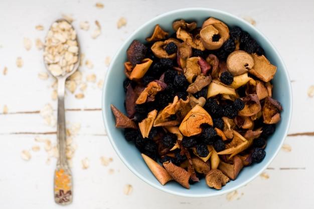 Een eetlepel havermout is een wit houten bijna blauw bord met gedroogde appels en bessen. gezond eten.
