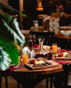 Een eettafel met voedsel en frisdranken in een restaurant.