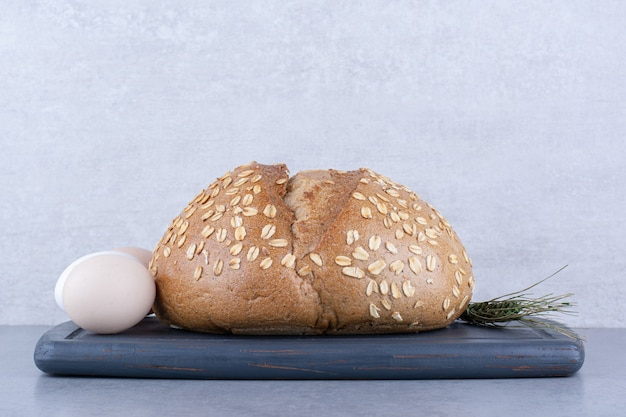 Een ei, een brood en een enkele tarwesteel op een bord op een marmeren ondergrond