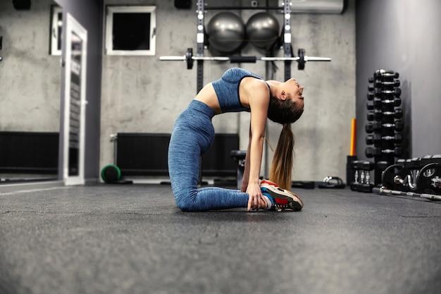 Een elastische vrouw in goede fysieke conditie rekt de spieren van het lichaam in de sportschool