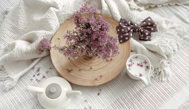 Een elegant en delicaat huisstilleven met lentebloemen en een drankje in een kopje.
