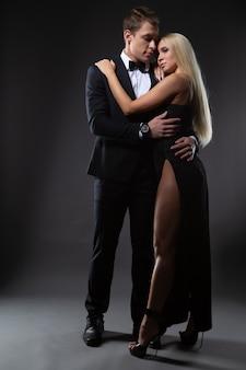 Een elegant paar omhelst elkaar zachtjes en kijkt elkaar aan.