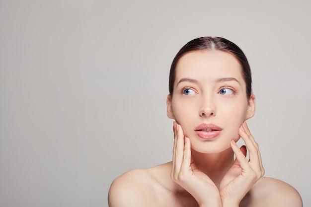 Een elegant verfijnd meisje met volle lippen, haar en stralende schone delicate huid op de. dame die kant bekijkt. spa, cosmetologie. goed verzorgde vrouw. gezichtsverzorging.