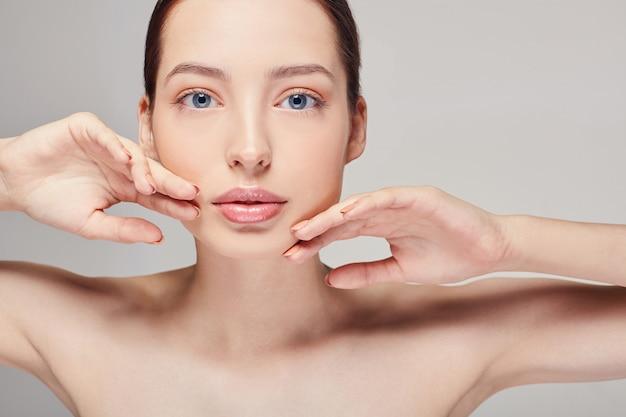 Een elegant verfijnd mooi meisje met volle lippen, donker haar en stralende schone delicate huid op de grijze.