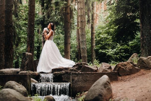Een elegante bruid in een witte jurk en handschoenen met een boeket staat bij een beek in het bos, genietend van de natuur