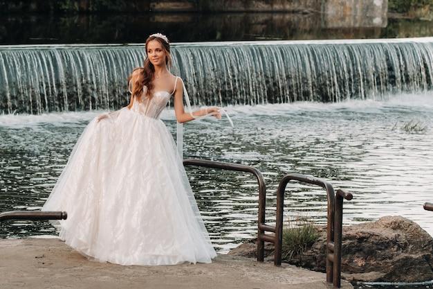 Een elegante bruid in een witte jurk en handschoenen staat aan de rivier in het park, genietend van de natuur