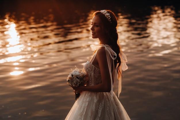 Een elegante bruid in een witte jurk en handschoenen staat aan de rivier in het park met een boeket, genietend van de natuur bij zonsondergang. een model in een trouwjurk en handschoenen in een natuurpark. wit-rusland.