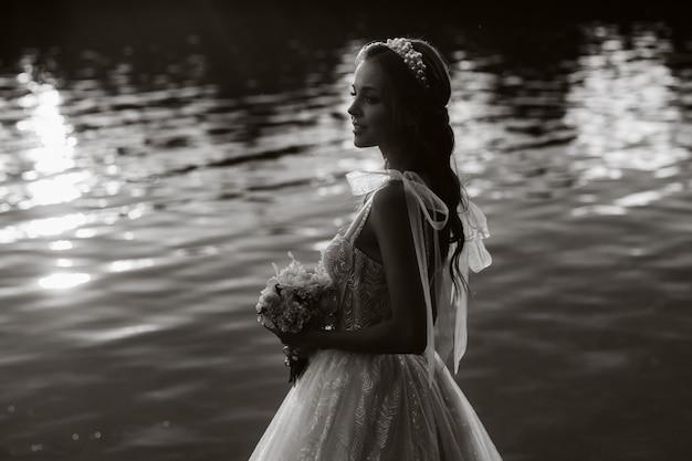 Een elegante bruid in een witte jurk en handschoenen staat bij de rivier in het park met een boeket