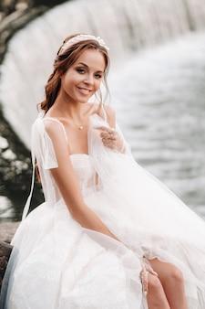 Een elegante bruid in een witte jurk, handschoenen en blote voeten zit in de buurt van een waterval in het park en geniet van de natuur.